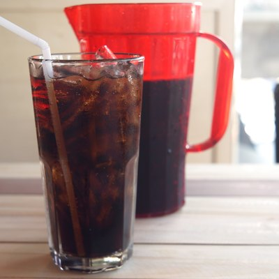 glass of cola and red jar on wooden background