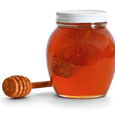 jar of honey with dipper
