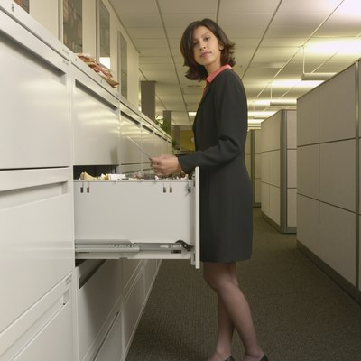 Young woman standing in front of a filing cabinet