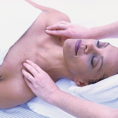 Woman getting massage, lying on back with eyes closed