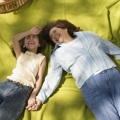 Mother and daughter laying on picnic blanket