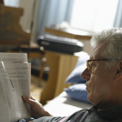 Mature man reading newspaper, close up