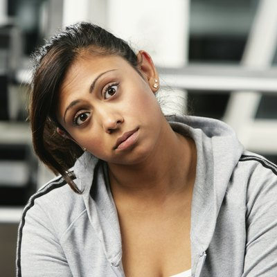 Portrait of a young woman sitting in a gym