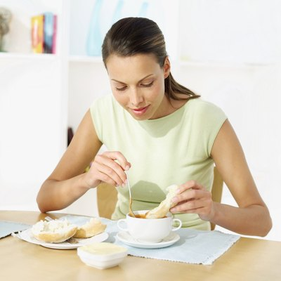 Young woman dipping a piece of bread in a bowl of tomato soup