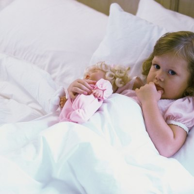 High angle view of a baby girl with a doll lying in bed