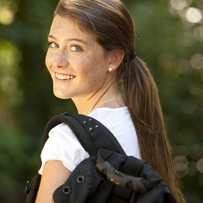 young girl with backpack looking over shoulder