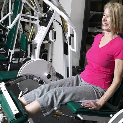 Senior woman lift leg weights in gym, smiling