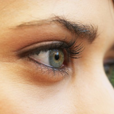 Young woman wearing eye make-up, high section, close-up