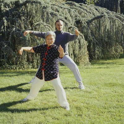 Man and woman practising tai chi in park
