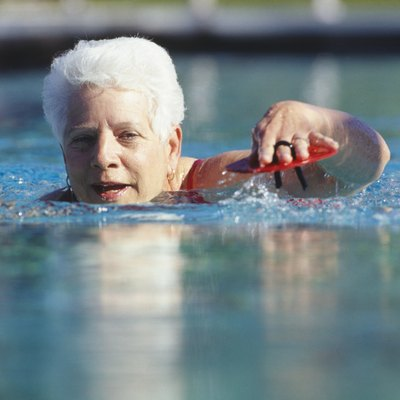 Senior woman swimming in outdoor pool, surface view
