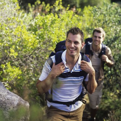 Two young men hiking with rucksacks, smiling