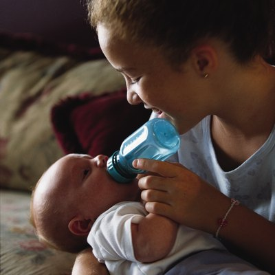 A caucasian older sister bottle feeds her little baby brother