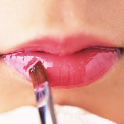 A Woman Applying Pink-Colored Lip Gloss, Front View, Differential Focus