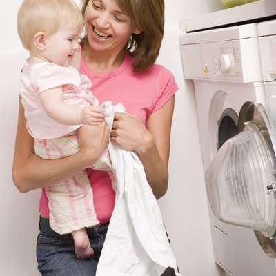 Mother holding baby and doing laundry