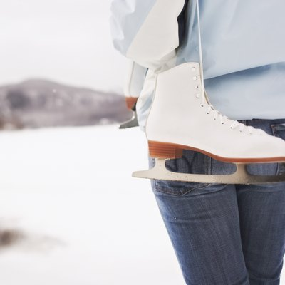 Back view of woman holding ice skates