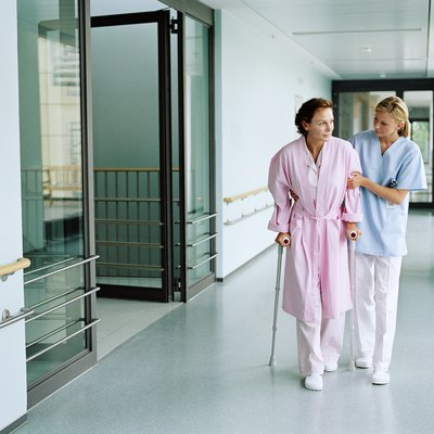 Nurse holding female patient using crutches in hospital corridor