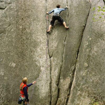 Woman holding rope, looking upward at partner climbing rock wall