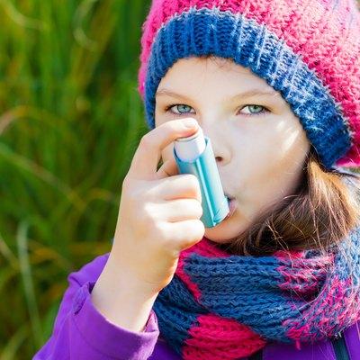Girl Using Asthma Inhaler on an autumn day