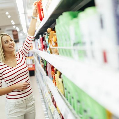 Beautiful woman buying body care products in supermarket