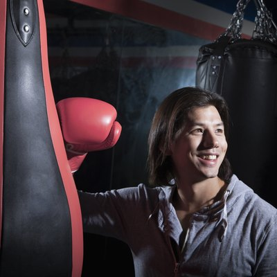 Portrait of smiling young man at the boxing gym leaning on punching bag