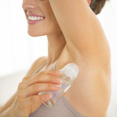 Closeup on happy young woman applying deodorant