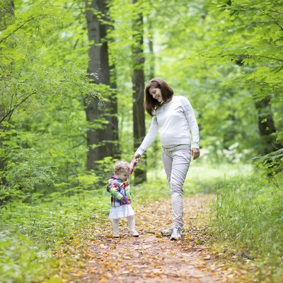 Beautiful pregnant woman and her baby daughter walking in park
