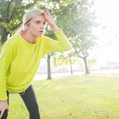 Active exhausted blonde pausing after running