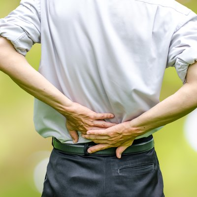 close up of a  man holding his back in pain.