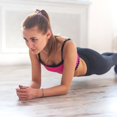 Slim fitnes young girl with ponytail doing planking exercise indoors