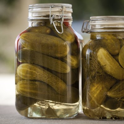 Glass jars of homemade canned  cucumbers on the outdoors kitchen
