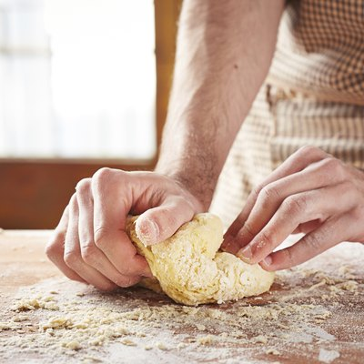 Hands baking dough on wooden table