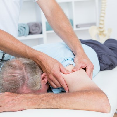 Physiotherapist doing shoulder massage to his patient