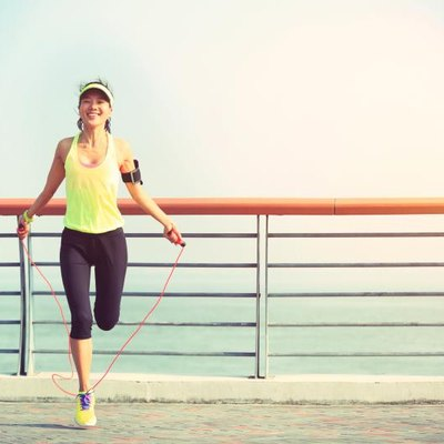 young woman jumping rope at  seaside