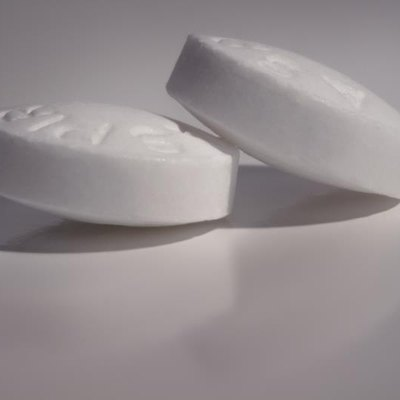 A macro image of two tablets of aspirin on a shiny reflective surface