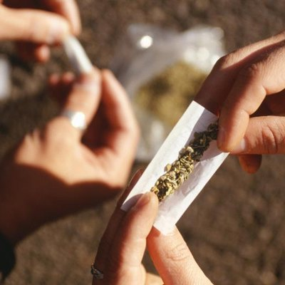 People rolling joints on street, closeup of hands.