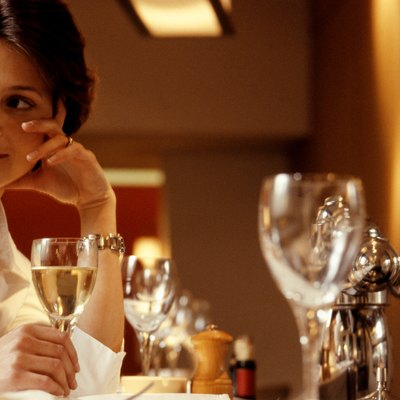 Woman sitting at table in restaurant, holding glass of wine, close-up