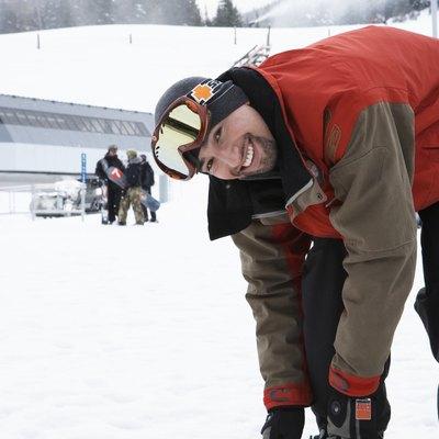 Man adjusting snowboard at base of mountain, smiling, portrait