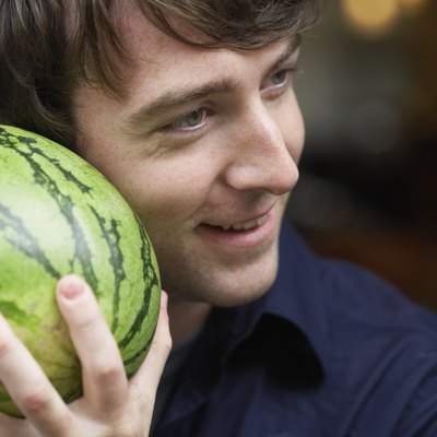 Young man holding watermelon up to ear, smiling, close-up