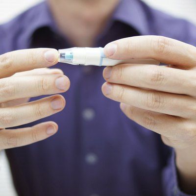Closeup of young man using checking level of blood sugar