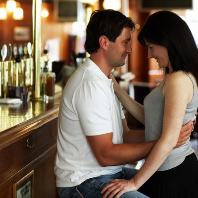 Woman standing between legs of man sitting on bar stool, face to face