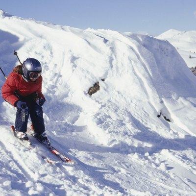Girl (12-13) skiing down ski slope in mountains