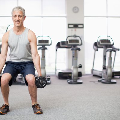 Portrait of smiling man doing squats with dumbbells in gymnasium
