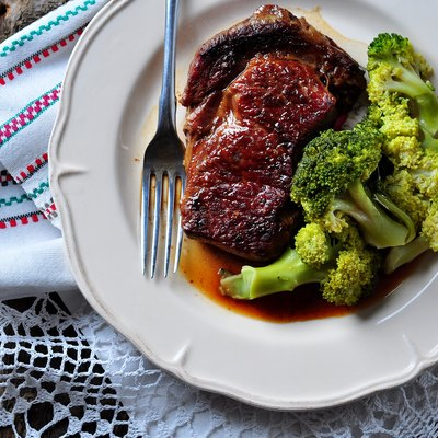 Grilled ribeye steak with boiled broccoli in olive oil