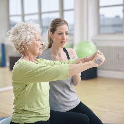 Senior woman training in the gym with a personal trainer