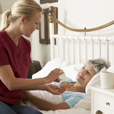 Health Visitor Giving Senior Woman Medication In Bed