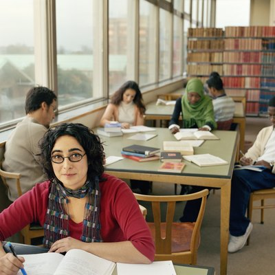 Students at tables in library work space, woman smiling, portrait