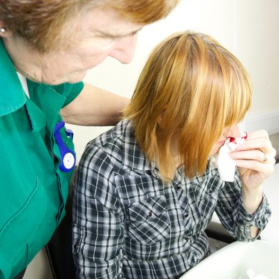 Paramedic nurse attends to a patient with a nose bleed