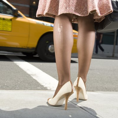 Woman with laddered stockings standing at roadside, low section