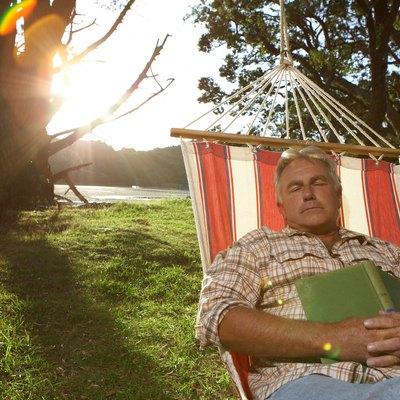 Mature man sleeping in hammock (lens flare)
