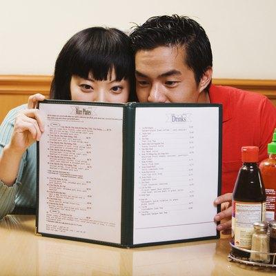 Asian couple reading menu at restaurant